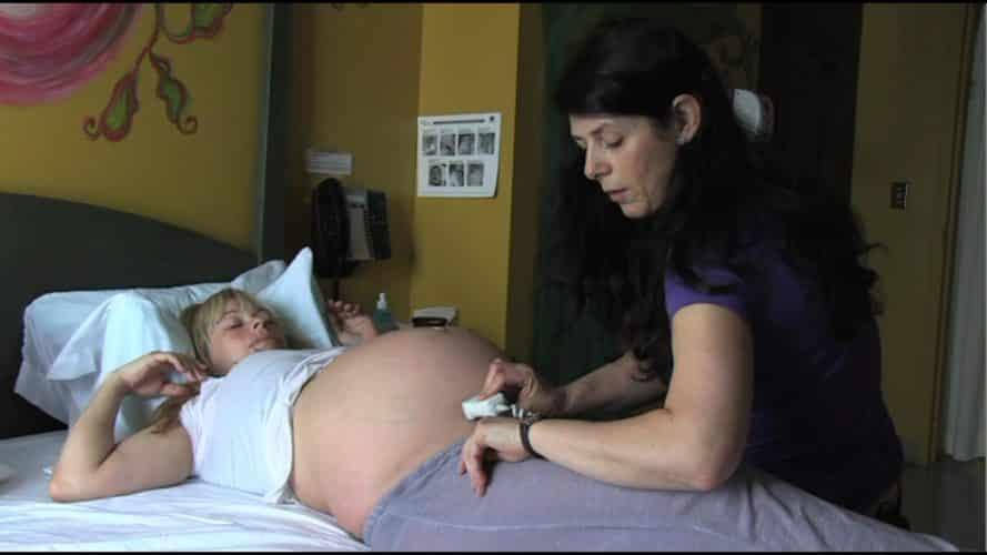 Photo - sage-femme qui écoute le coeur du bébé à l'accouchement